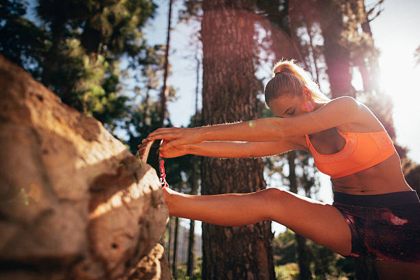 Fit woman athlete stretching leg on a nature trail run Fit and healthy woman athlete preparing for a morning trail run in nature by using a rock to stretch her leg with bright early sunflare shining over her shoulder hamstring stock pictures, royalty-free photos & images
