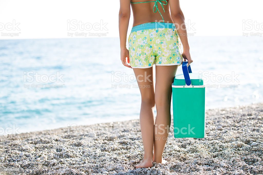 Fit woman carrying cooler box,portable fridge on the beach stock photo