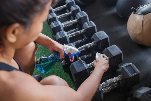 Fit woman cleaning dumbbell with disinfectant spray stock photo