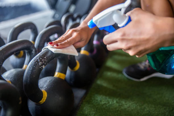 Fit woman cleaning kettlebell before work out at gym stock photo