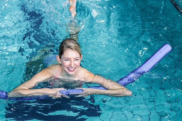 Fit woman doing aqua aerobics with foam rollers - foto stock