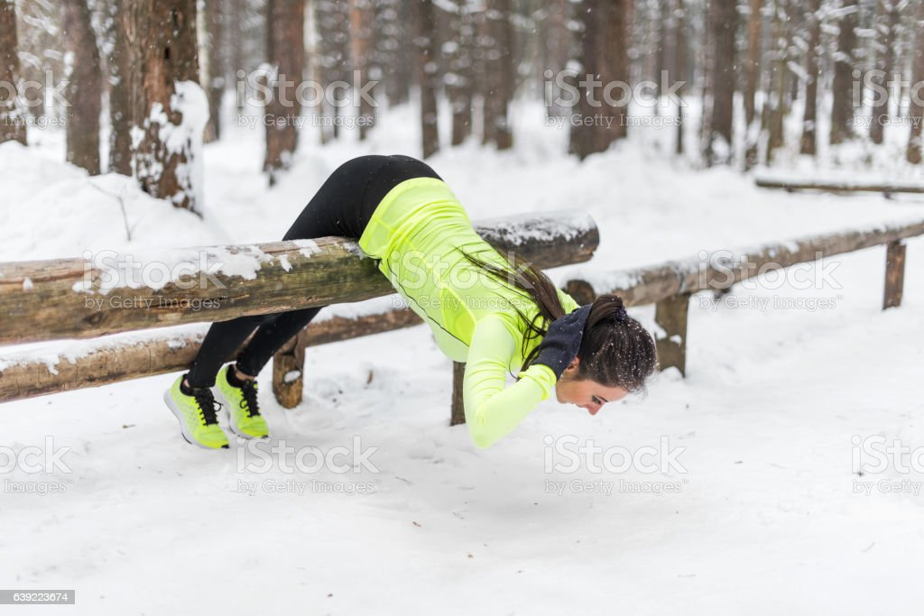Fit woman doing back extension exercise outdoors in woods. Female stock photo