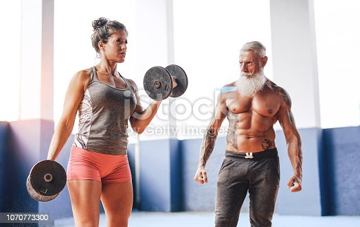Fit woman doing curl biceps exercise with dumbbells in fitness gym center - Female athlete training with her personal trainer inside wellness sport club - Workout and sportive motivation concept