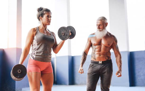 fit woman locken bizeps übung mit hanteln im fitnessstudio fitnesscenter - sportlerin training mit ihrem personal trainer in wellness-sport-club - training und sportliche motivation konzept - alte tattoos stock-fotos und bilder