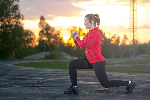 fit woman doing frontal lunges outdoors - spagat stock-fotos und bilder