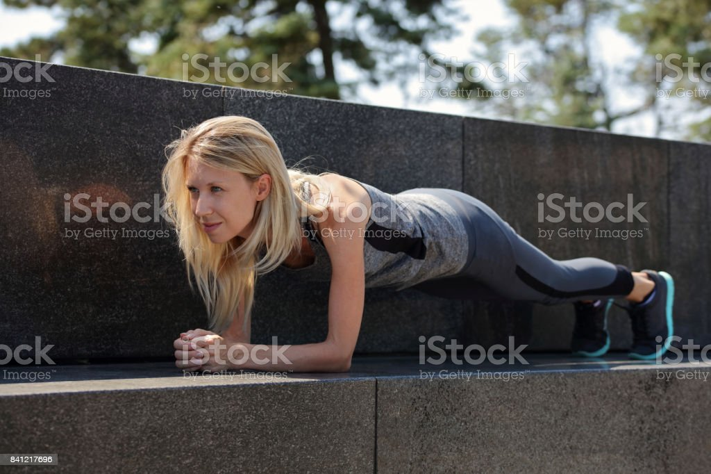 Fit woman doing plank exercise outdoor. Sport, fitness, active lifestyle stock photo