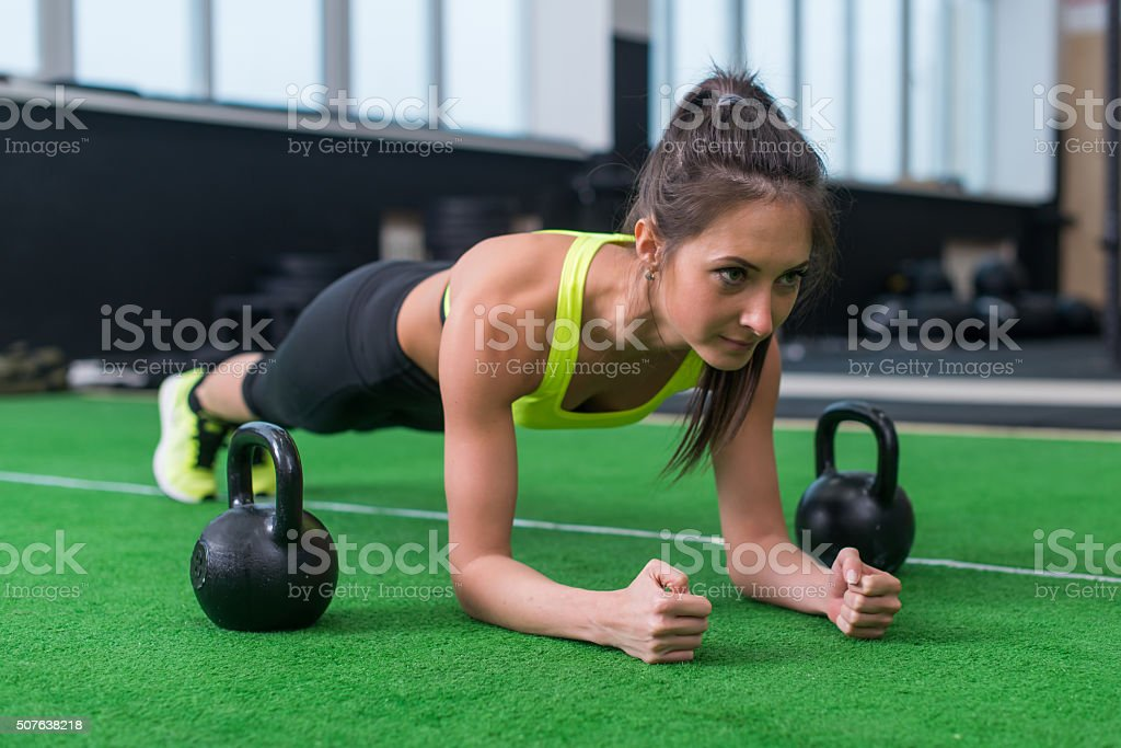 Fit woman doing plank exercise working on abdominal muscles in stock photo