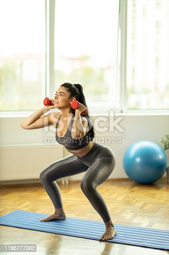 1035512048istockphoto Fit woman doing squats with dumbbells 1195777002