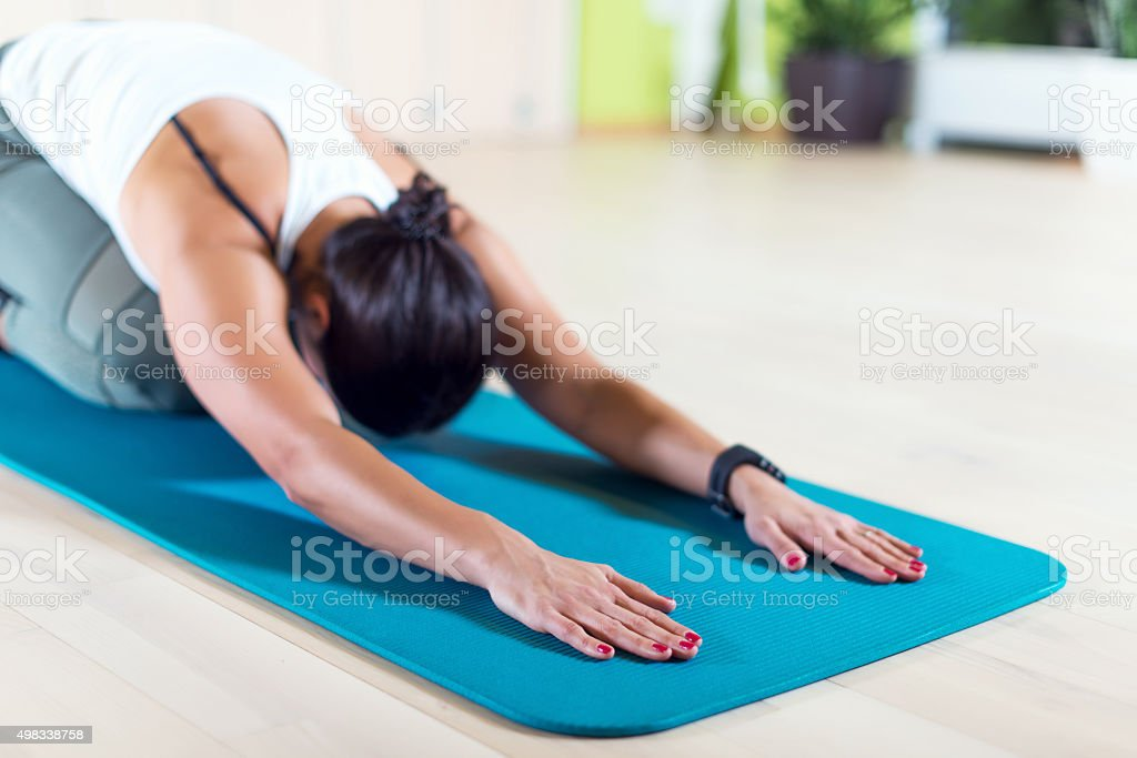 Fit woman doing stretching pilates exercises in fitness studio stock photo