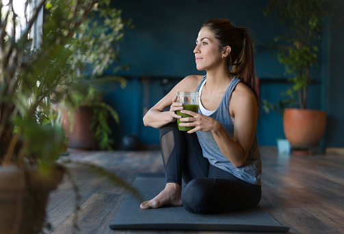 Portrait of a fit Latin American woman drinking a green detox smoothie at the gym - healthy lifestyle concepts