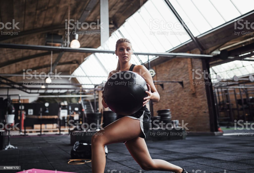 Fit woman exercising with a fitness ball at the gym stock photo