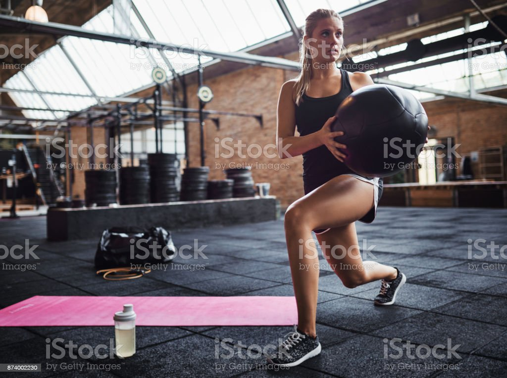 Fit woman exercising with a swiss ball at the gym stock photo