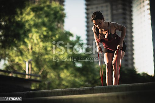 One beautiful fit woman exercising with rope in city park.