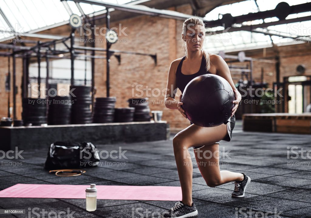 Fit woman focused on working out with a ball stock photo