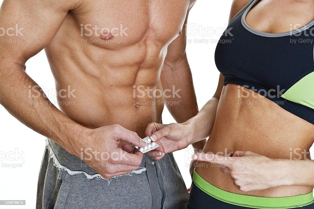 Fit woman handing man pills royalty-free stock photo