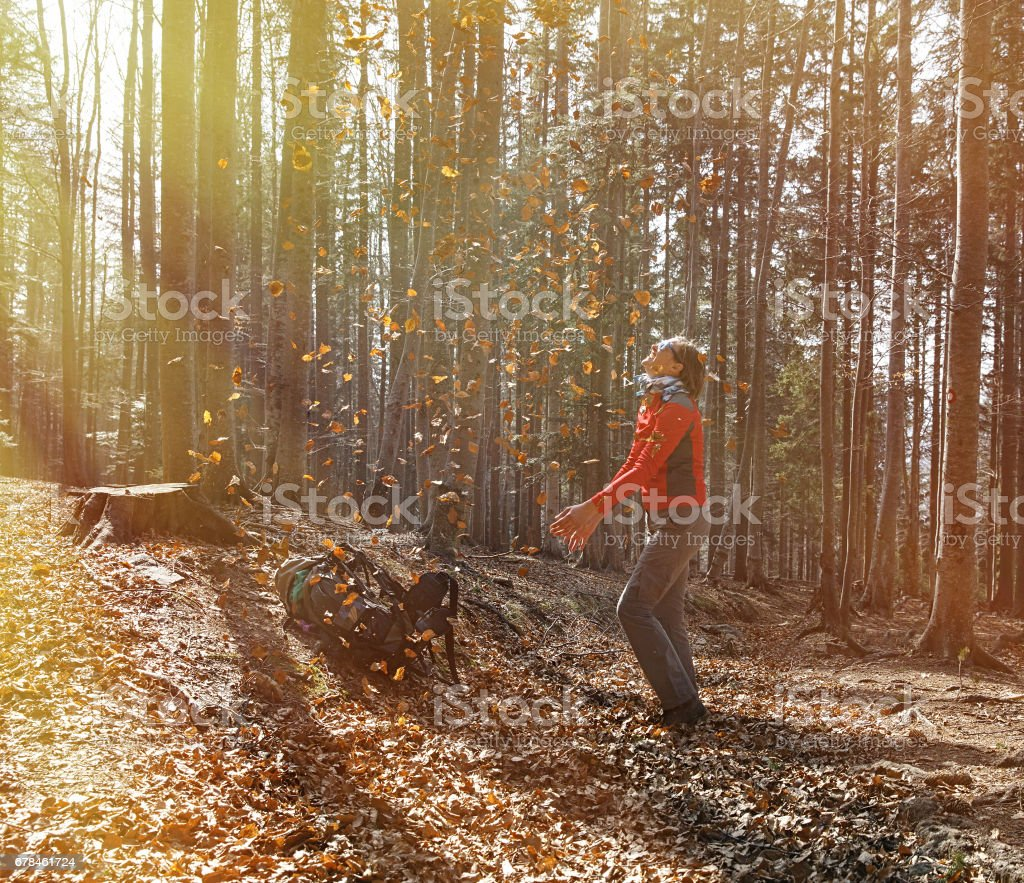 Fit woman hiker enjoying the nature, throwing leaves royalty-free stock photo