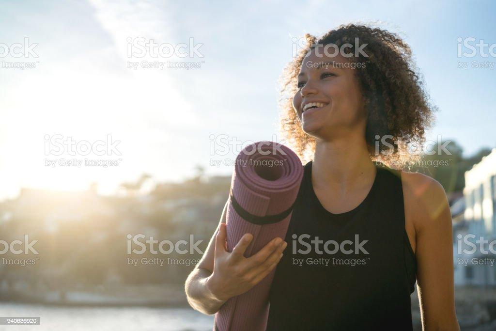 맞는 여 자가 해변에서 요가 매트를 들고 - 로열티 프리 건강한 생활방식 스톡 사진