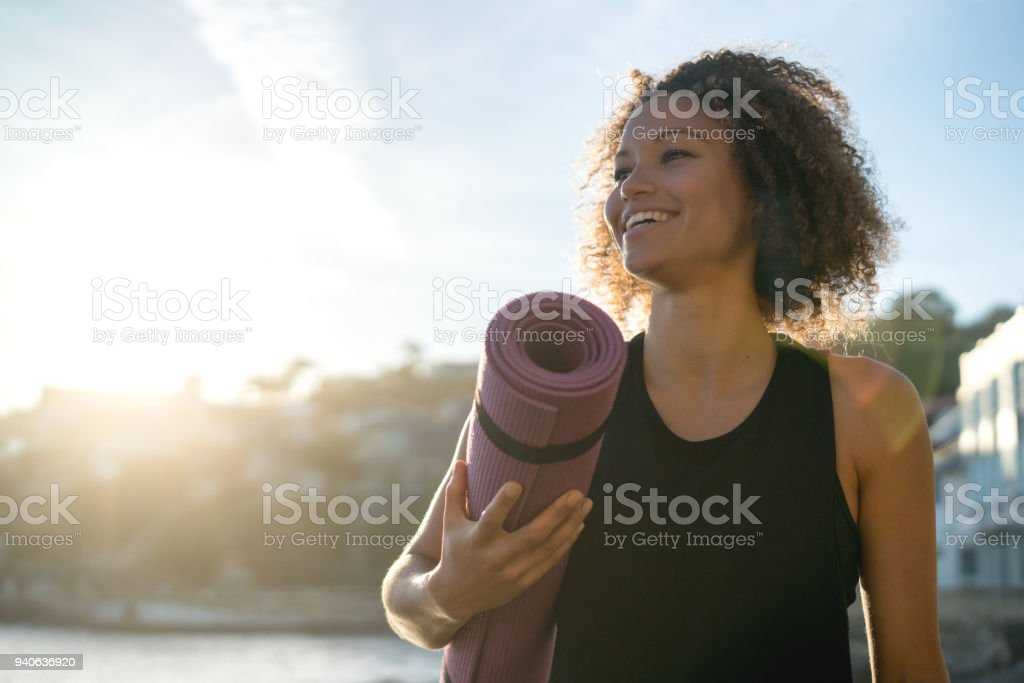 Fit woman holding a yoga mat at the beach stock photo