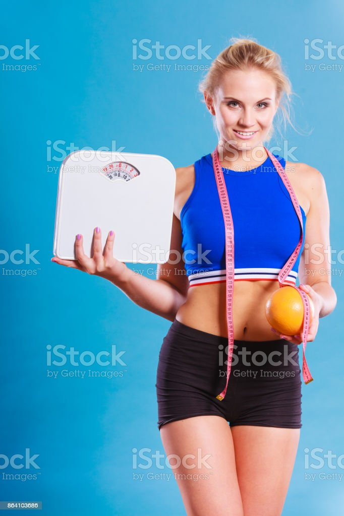 Fit woman holds weight scale grapefruit royalty-free stock photo