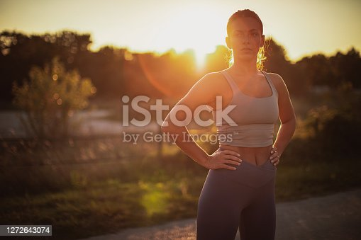 One young attractive fitness woman in sports wear standing outdoors.