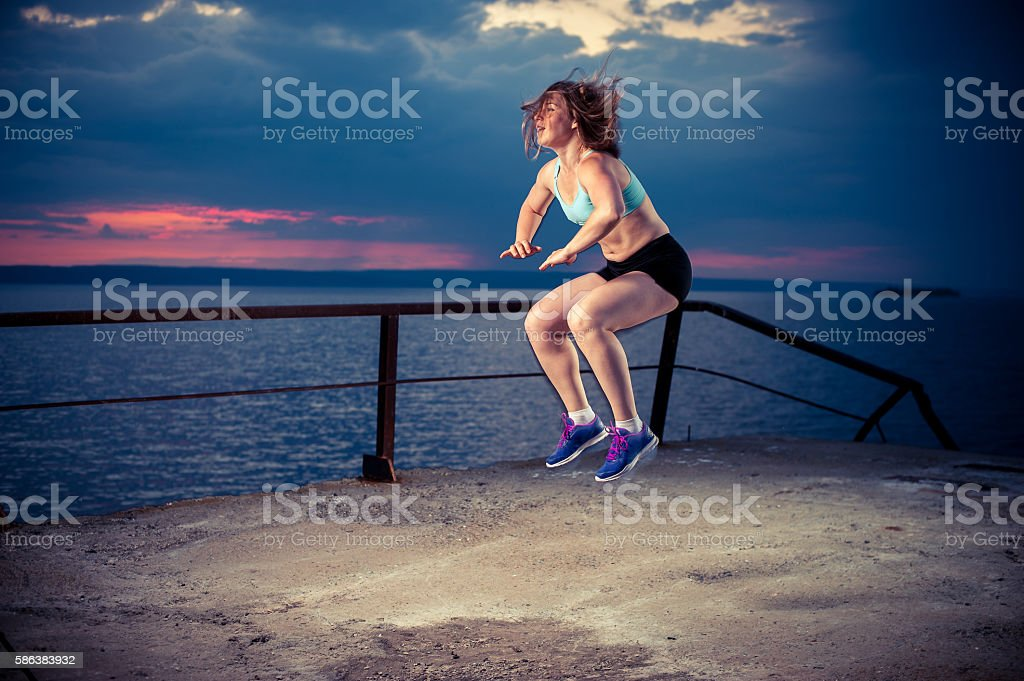 Fit woman in sportswear doing squat jumps stock photo