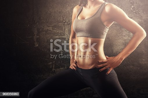 istock Fit woman in stretching pose with flat stomach and strong muscles 968356960