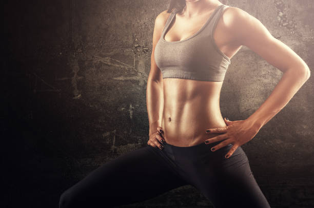 Fit woman in stretching pose with flat stomach and strong muscles stock photo