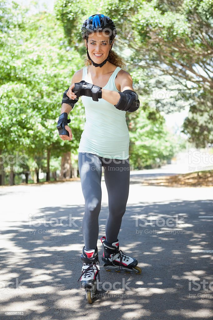 Fit woman inline skating through the park stock photo