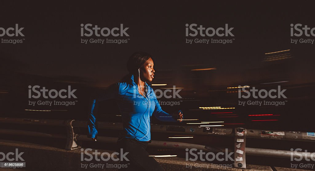 fit woman jogging at night through the city stock photo