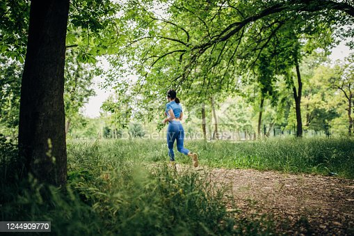 One young fit woman jogging in the park and listening music on headphones, rear view. Sports lifestyle.