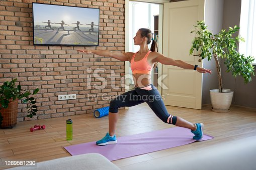 Fit sporty active young woman learning warrior yoga pose watching live streaming online workout exercise training weightloss class sport tv at home in living room. Fitness tutorial livestream concept