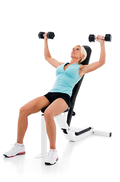 Fit woman lifting weights on weight bench stock photo