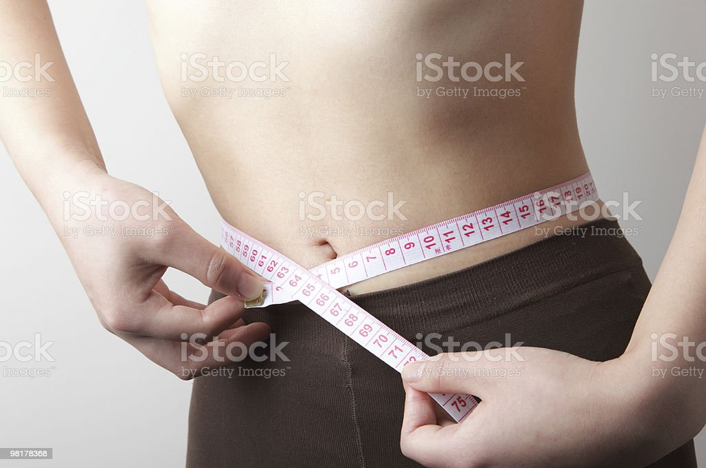 Fit woman measuring her waist royalty-free stock photo
