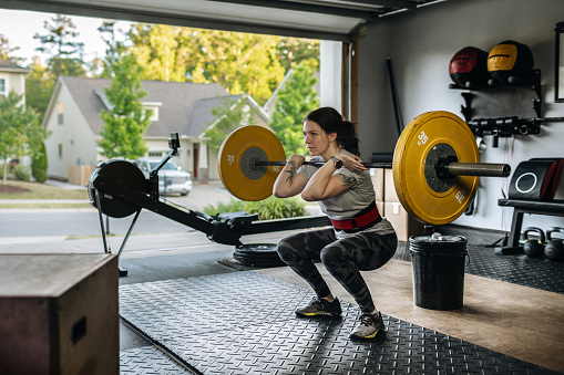 Photo of a fit woman performing a front squat with a heavy barbell in her home garage gym during covid-19 pandemic. Woman lifting a barbel and performing heavy powerlifting exercises. Power clean exercise. Focusing on core strength improvement.