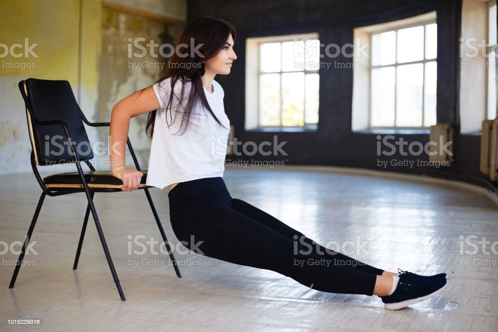 Fit woman performing reverse push ups using chair stock photo