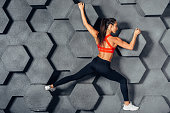 Fit woman posing like a climber hanging on decorative wall.