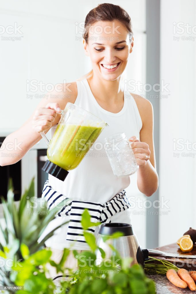 Fit woman pouring green cocktail stock photo