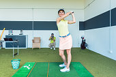 fit woman practicing golf swing during professional class indoors