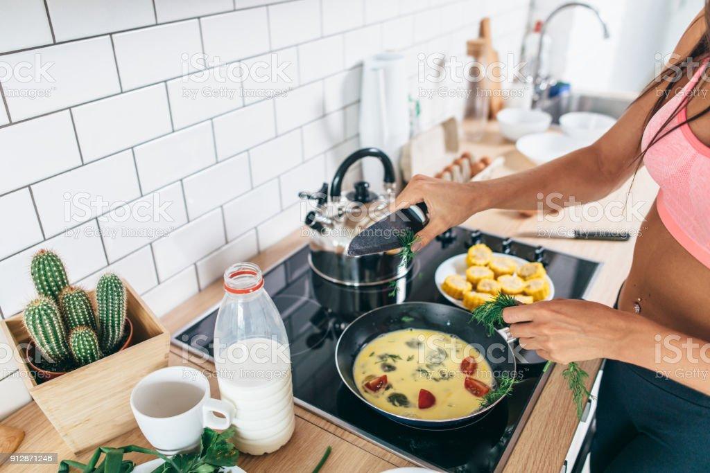 Fit woman preparing healthy breakfast in kitchen stock photo
