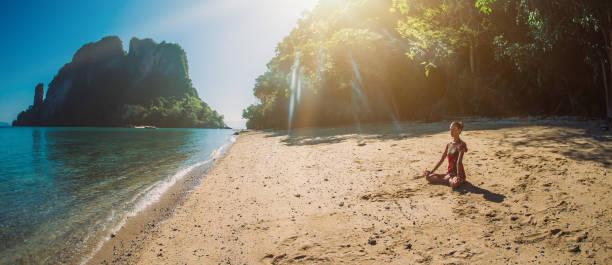 fit woman relaxing and practicing yoga outdoors by the sea - poprawna postawa zdjęcia i obrazy z banku zdjęć