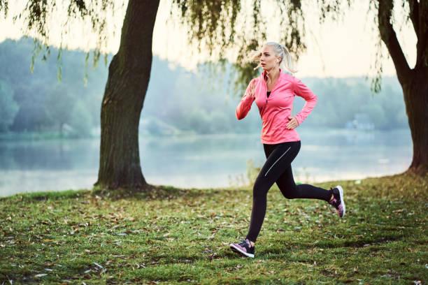 fit frau läuft bei nebligen herbstmorgen im park - joggerin stock-fotos und bilder