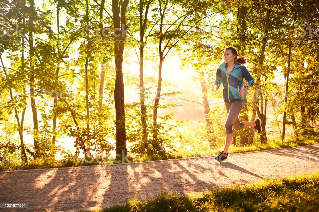 Fit woman running in the morning stock photo
