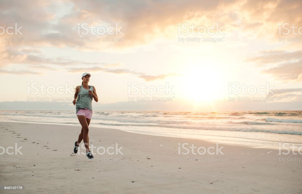 Fit woman running on the beach in morning stock photo
