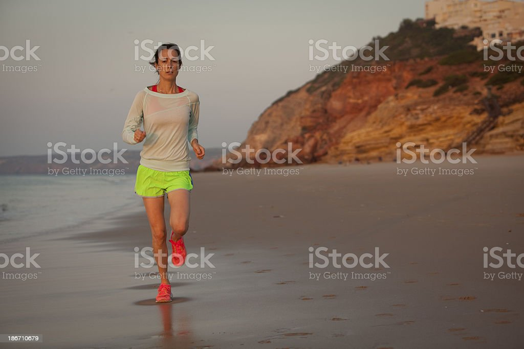 Fit woman running on the beach in Salema Portugal royalty-free stock photo