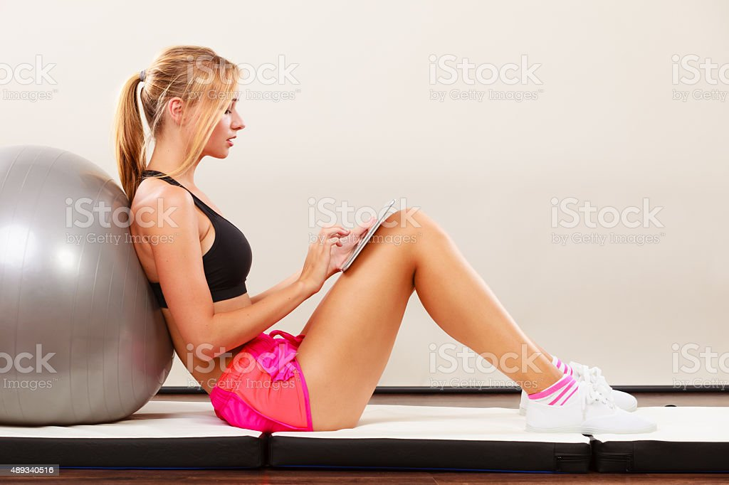 Fit woman sitting on floor with tablet pc stock photo