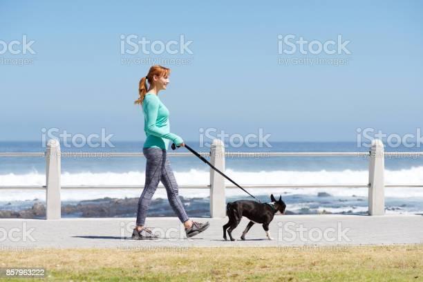 Fit woman smiling and walking dog on path by sea picture id857963222?b=1&k=6&m=857963222&s=612x612&h=wre4iytpqxyzqg2y57wl ispeya1tpq miwgakvykk4=