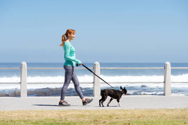 Fit woman smiling and walking dog on path by sea picture id857963222?b=1&k=6&m=857963222&s=612x612&w=0&h=nw2oz7yspz93ajf0odaqpsiwjvdrmf1gps iojbqthc=