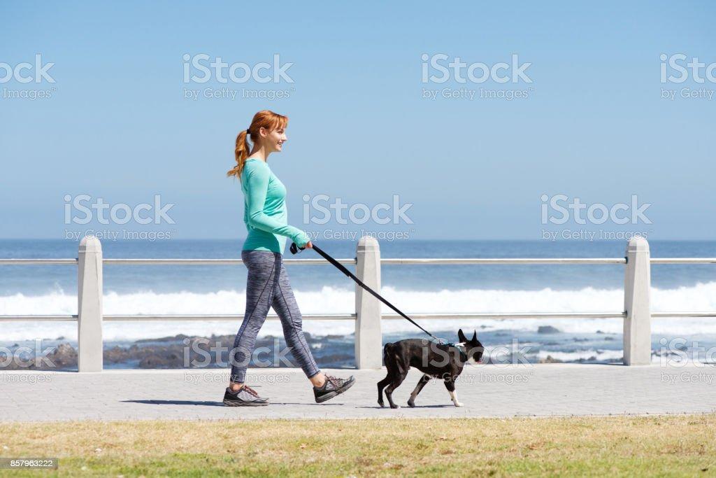 fit la femme souriante et chien marche sur le chemin d'accès par la mer - Photo