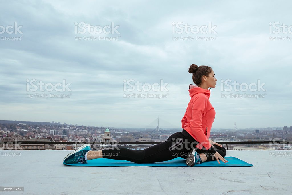 fit woman stretching and exercising on the rooftop stock photo
