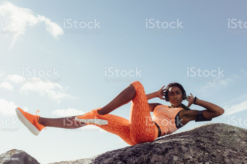 Fit woman stretching at the beach stock photo